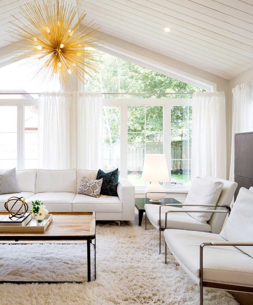 Living room space with pitched ceiling and gold starburst chandelier.