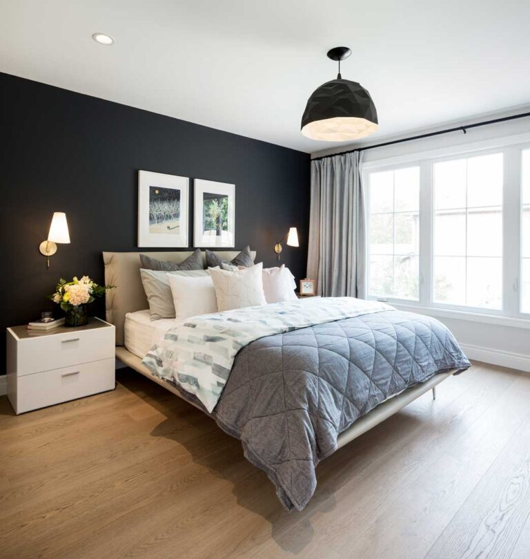 Bedroom with black accent wall and white oak floors.