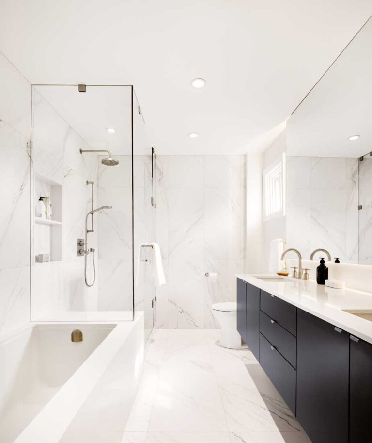 White bathroom with bathtub and black cabinets topped with white marble.