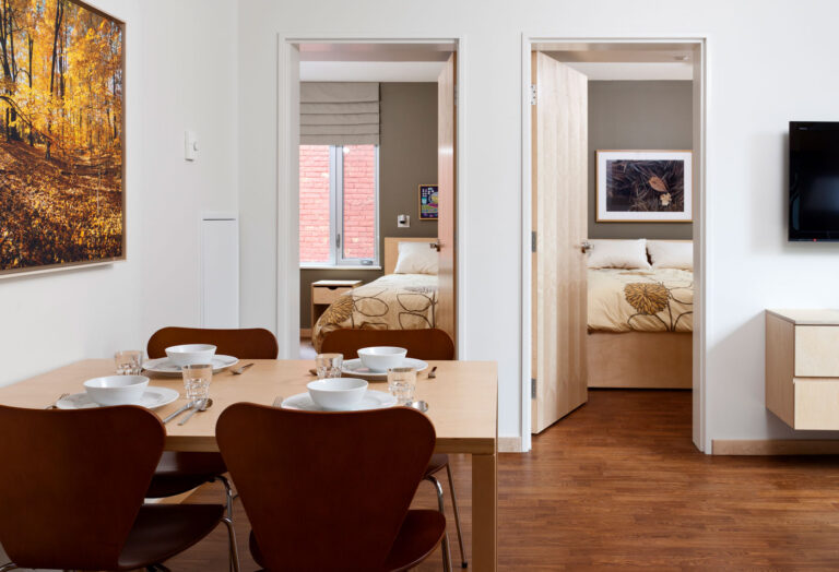 Suite with kitchen table and chairs and two bedrooms for family.