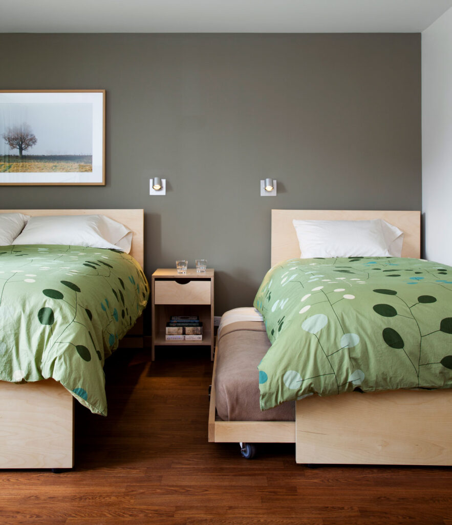 Twin beds with pale green bedding and a soft green wall.