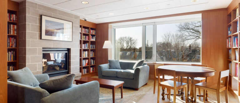 Library space at Ronald McDonald house with dark gold walls and light blue couches.