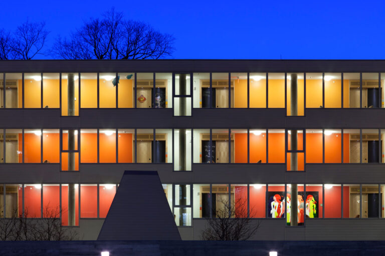 Exterior night time view of Ronald McDonald House with floors painted in red, orange and yellow forming a gradient.