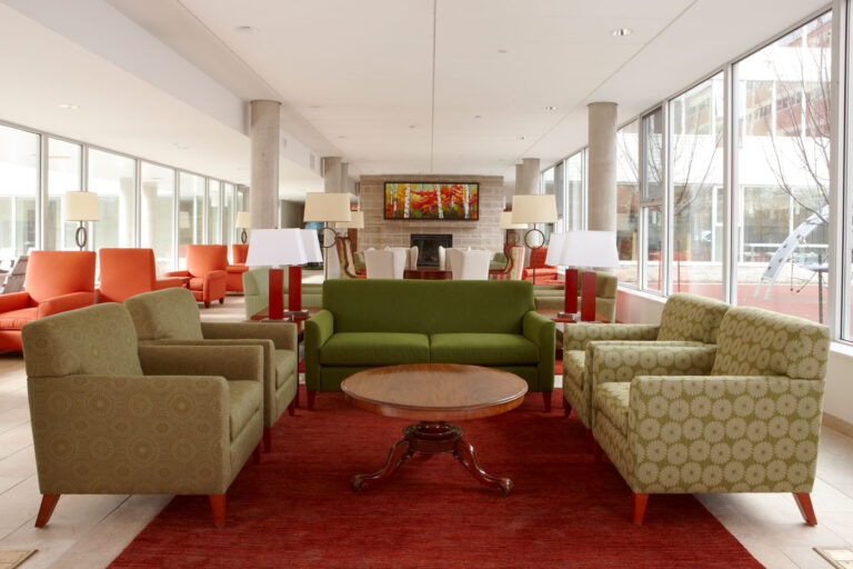 Common living room space at Ronald McDonald House with red rug and green seating.