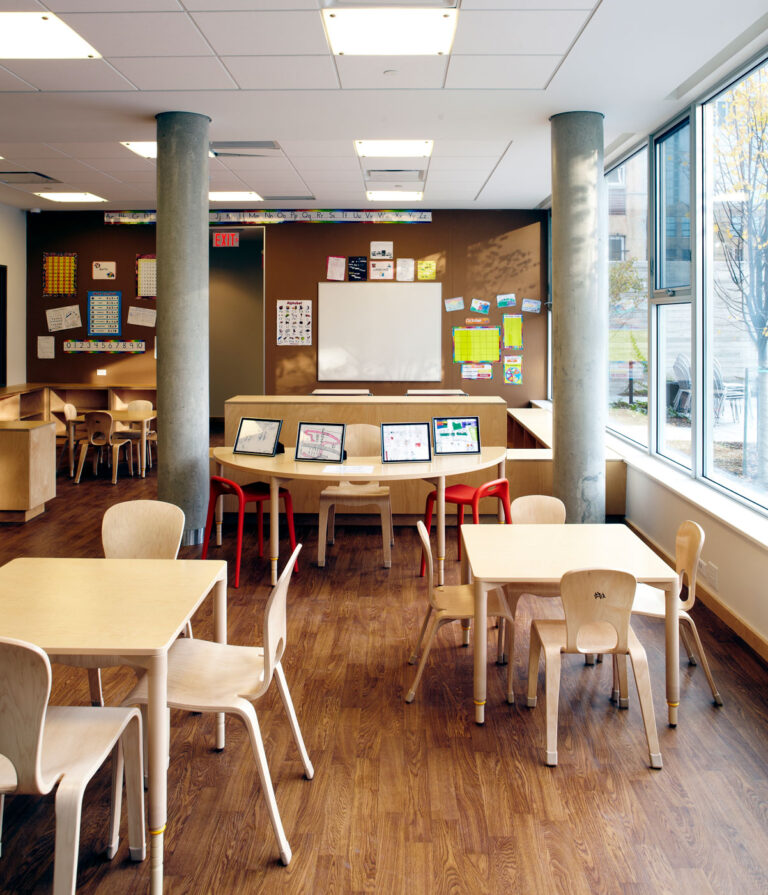 Classroom space with warm wood flooring and small wood tables for children.