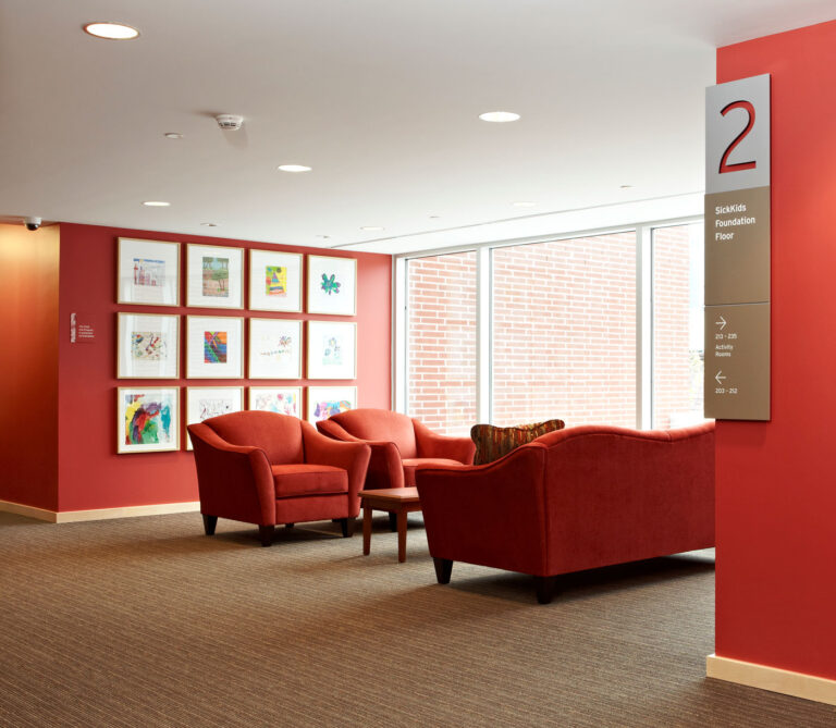 Living room space with red walls, red couches and pale brown carpeting. Large gallery wall with pictures in white frames.