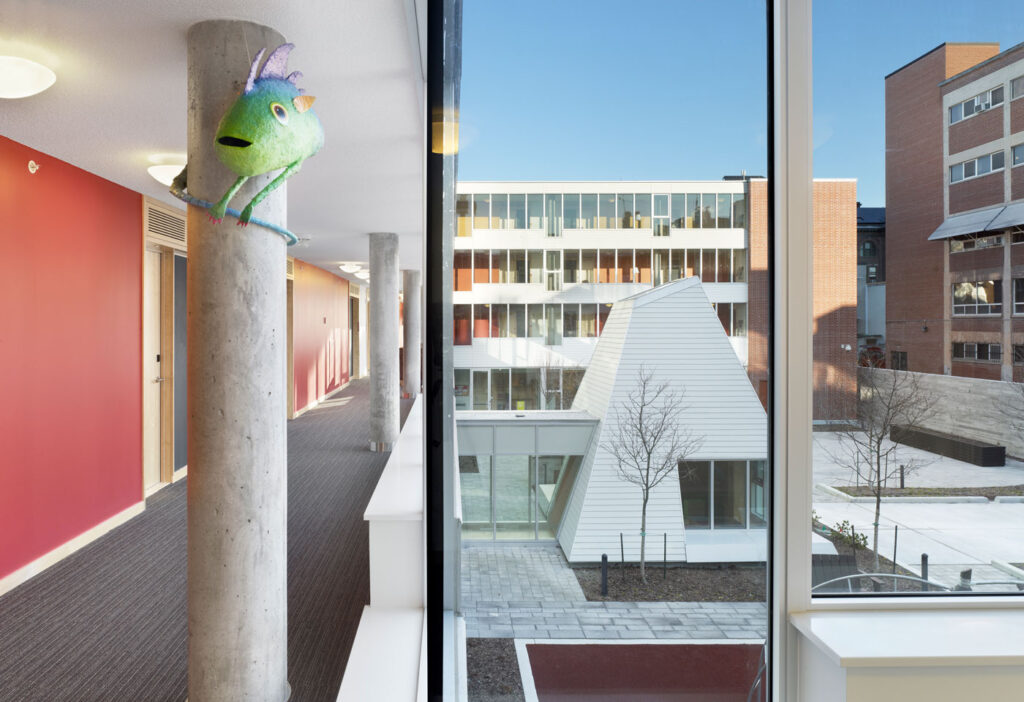 View from interior to exterior courtyard with additional view down a hallway.