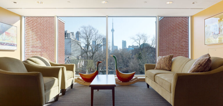 Living room space in a private suite with pale green couches and floor to ceiling windows.