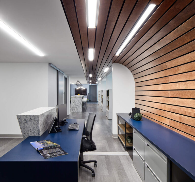 Blue reception desk with wood slatted accent wall behind.