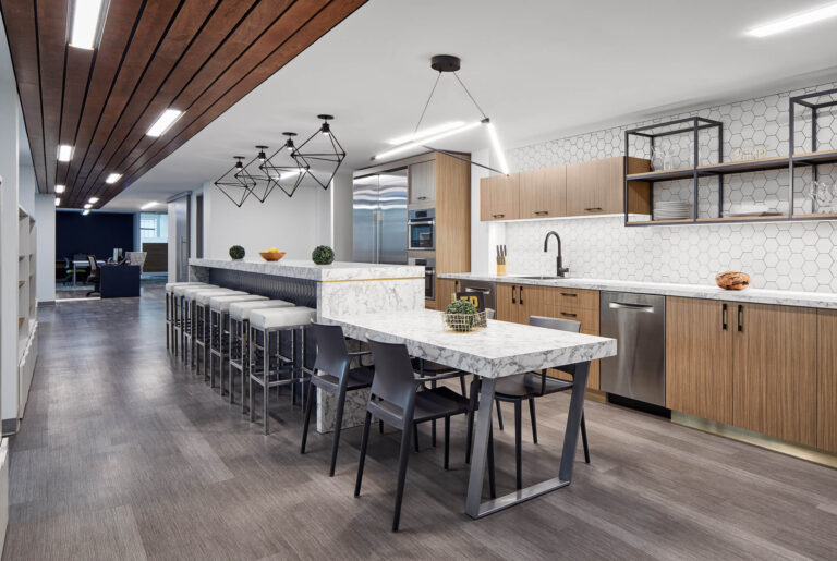Employee kitchen space with white topped island and black metal stools underneath.