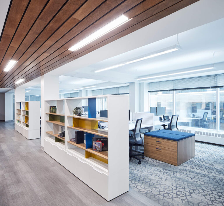 White shelving blocks off desk areas and acts as a privacy screen at this office.