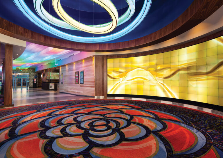 Carpet with a large scale floral pattern in casino lobby with a light fixture of concentric rings is suspended above.