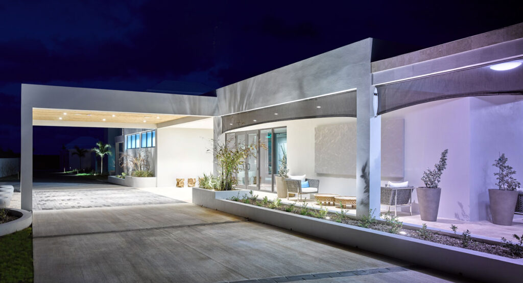 Exterior night view of a beautiful modern hotel with white walls and a covered awning for guests arriving by car.