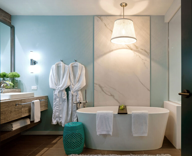 Bathroom with standing tub, turquoise walls and marble accent wall.