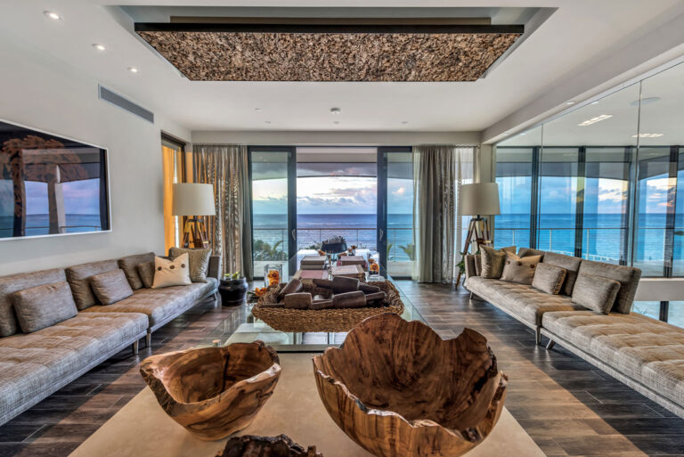 Serene lounge space with upholstered bench seating, and a view to the sea.