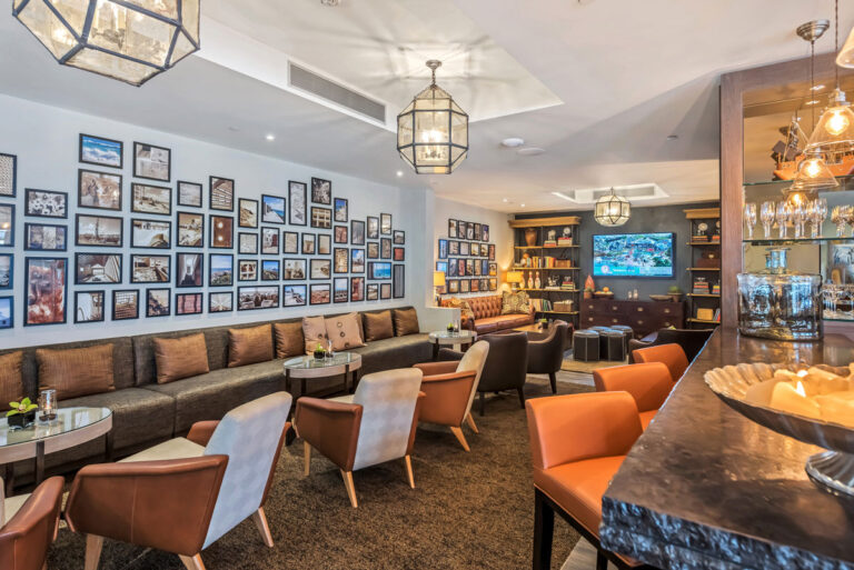 Resort bar area with upholstered bench seating and leather chairs with a gallery wall of classic british images.