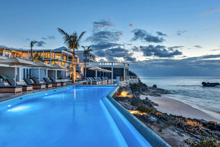 A swimming pool glows in the evening light, right on the beach of this resort area.