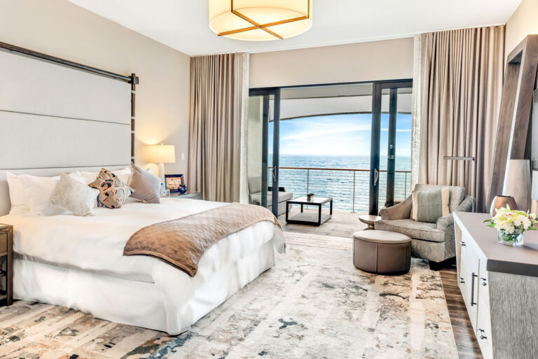 Serene hotel room with gray and taupe colours, lush white bedding and an unobstructed view of the sea.