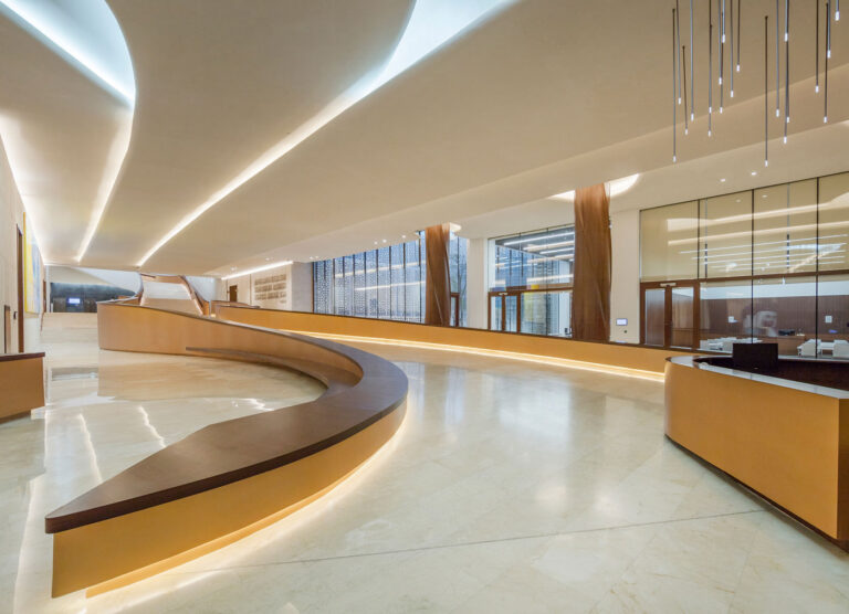 Curving ramp below grade with pale marble floors and gold railings with lighting underneath.