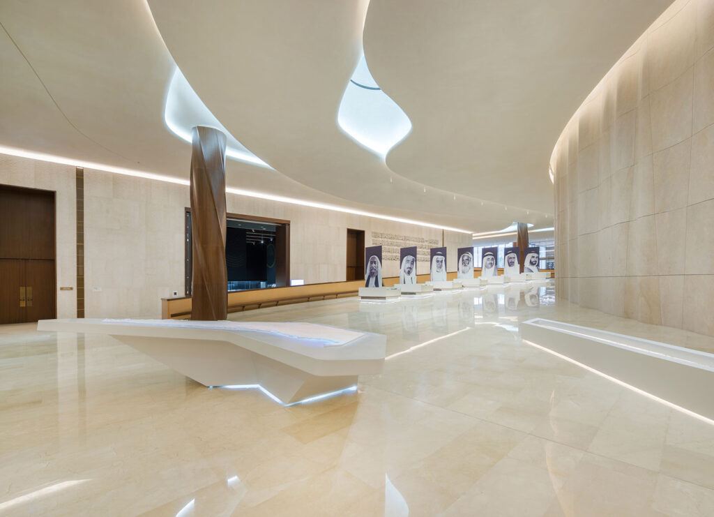 Marble and white exhibition area with white curving walls.