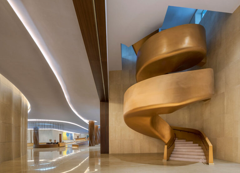 Organic curving staircase covered in copper coloured surfacing.