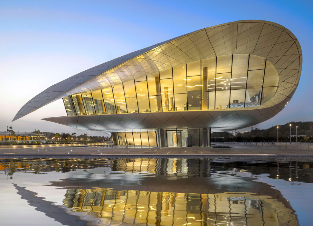 Evening view of Etihad Museum, with building curving over itself like a sheaf of paper.