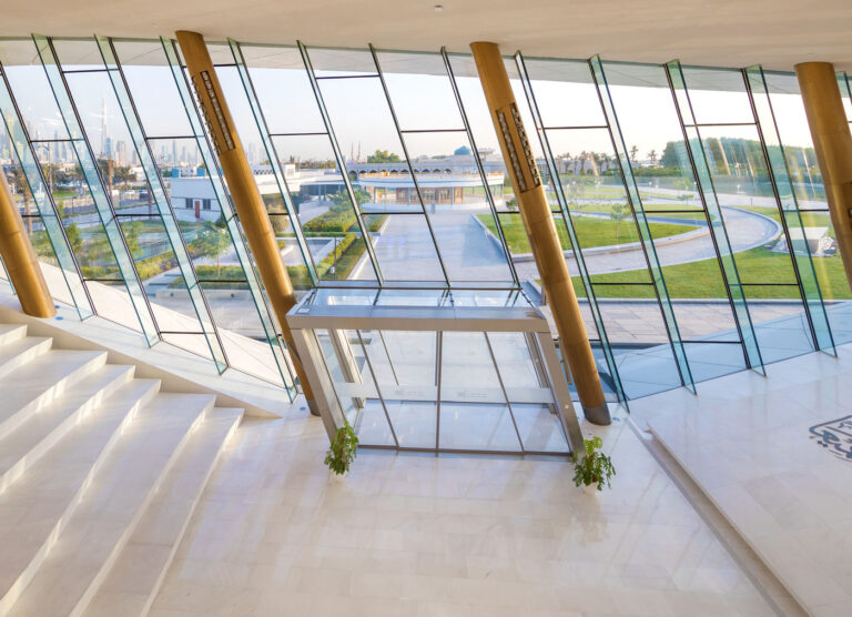 Marble covered entry to Etihad museum with diagonally leaning columns.