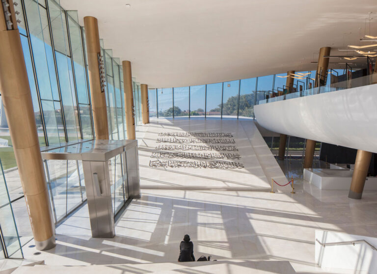 Marble covered atrium at Etihad Museum, with sloped floor of Declaration of Independence in Arabic.