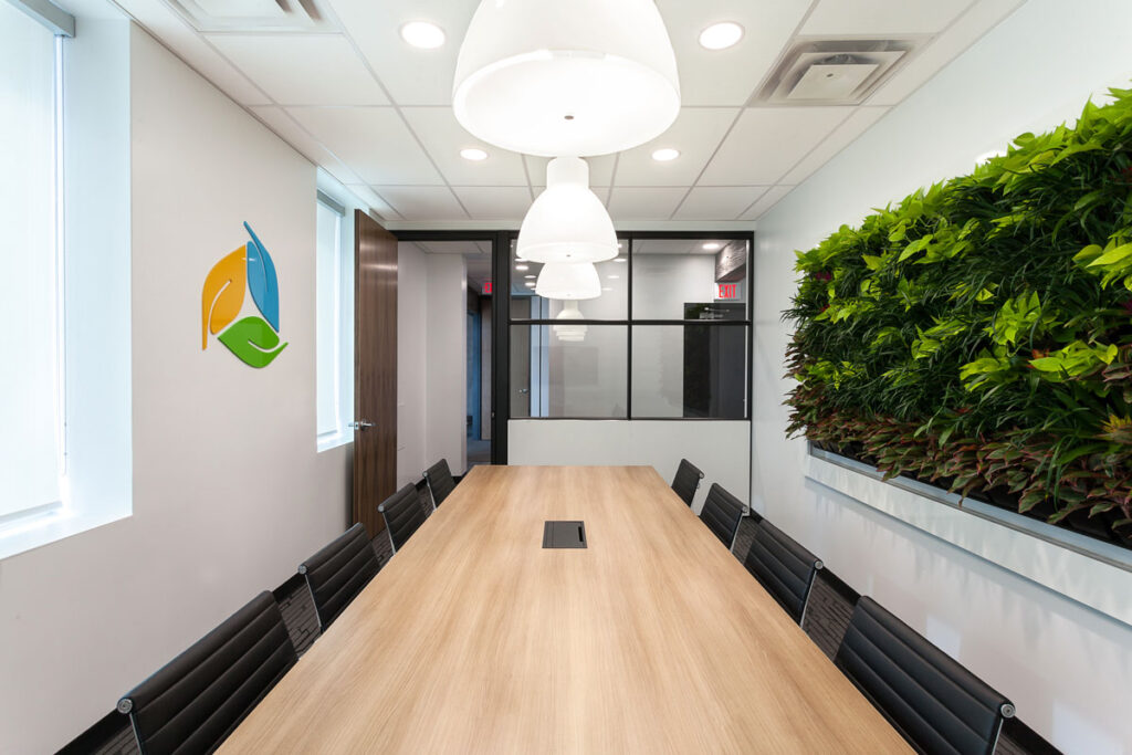 Meeting room with wood topped boardroom table, and living wall.