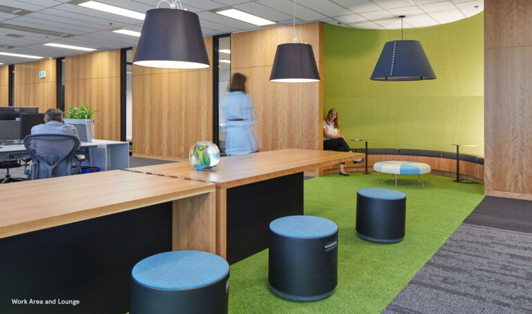 Casual meeting space with wood topped tables and small black and blue stools.
