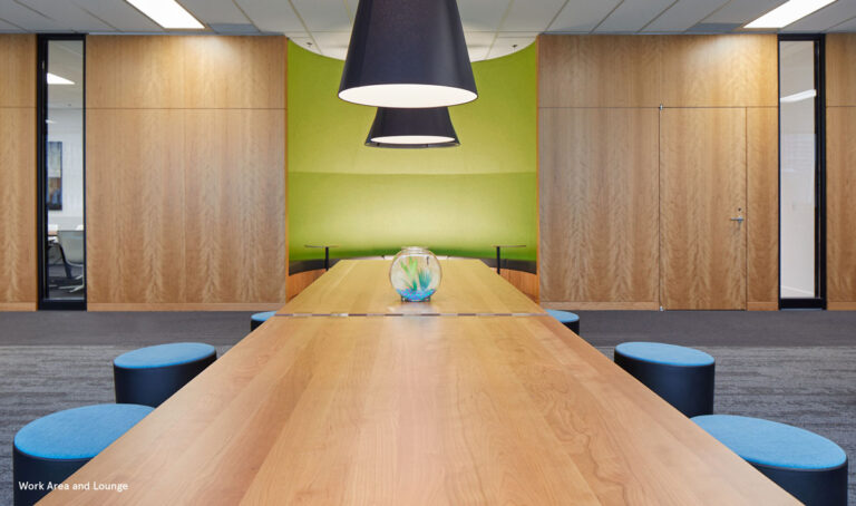 Warm wood meeting table with lamps with black shades overhead.
