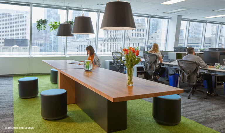 Meeting area with wood topped table and green carpet underneath.