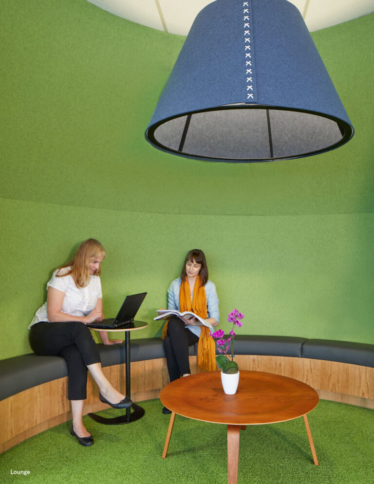 Round casual meeting area with soft green walls, bench seating and a large blue light fixture overhead.