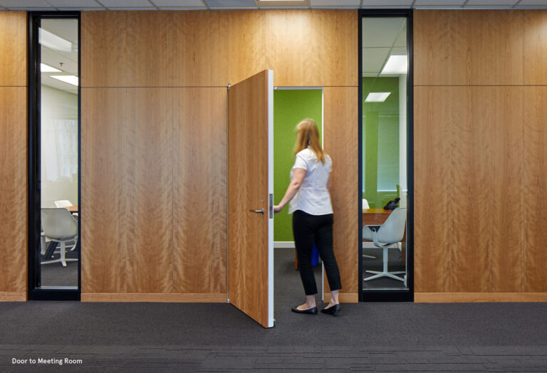 A person opens a door to a meeting room with full height windows rimmed in black.