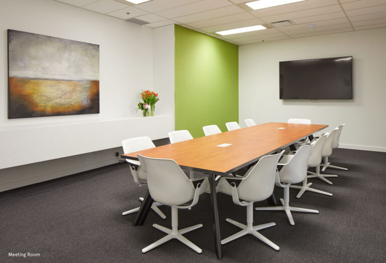 Meeting room at the Ontario College of Physiotherapists with white walls and a wood topped table.