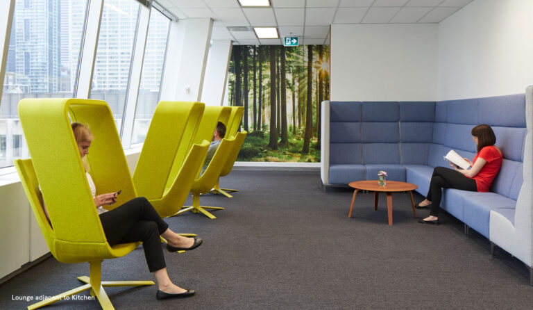 Lounge seating in acid green along a wall of windows across from a long seating area upholstered in blue.