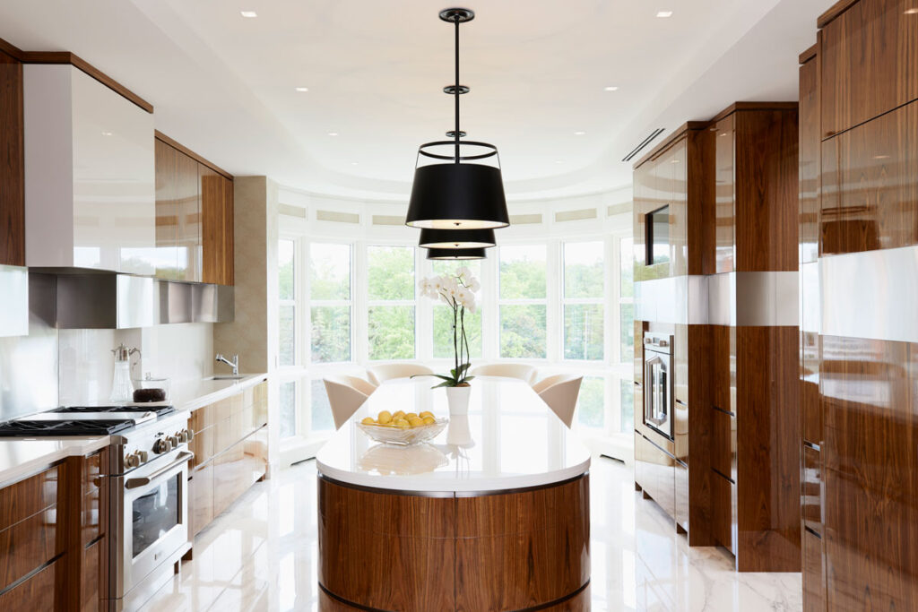 Luxe kitchen area with large curved island and maple brown cabinets.
