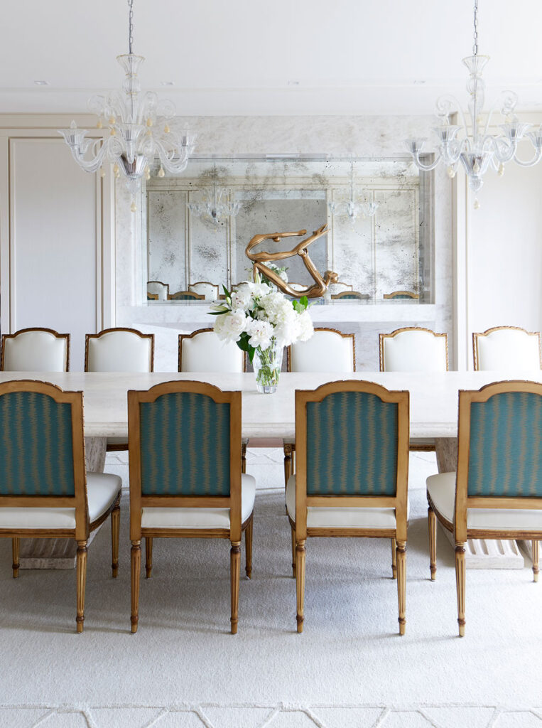 Serene white dining area with chairs upholdstered in white and green.