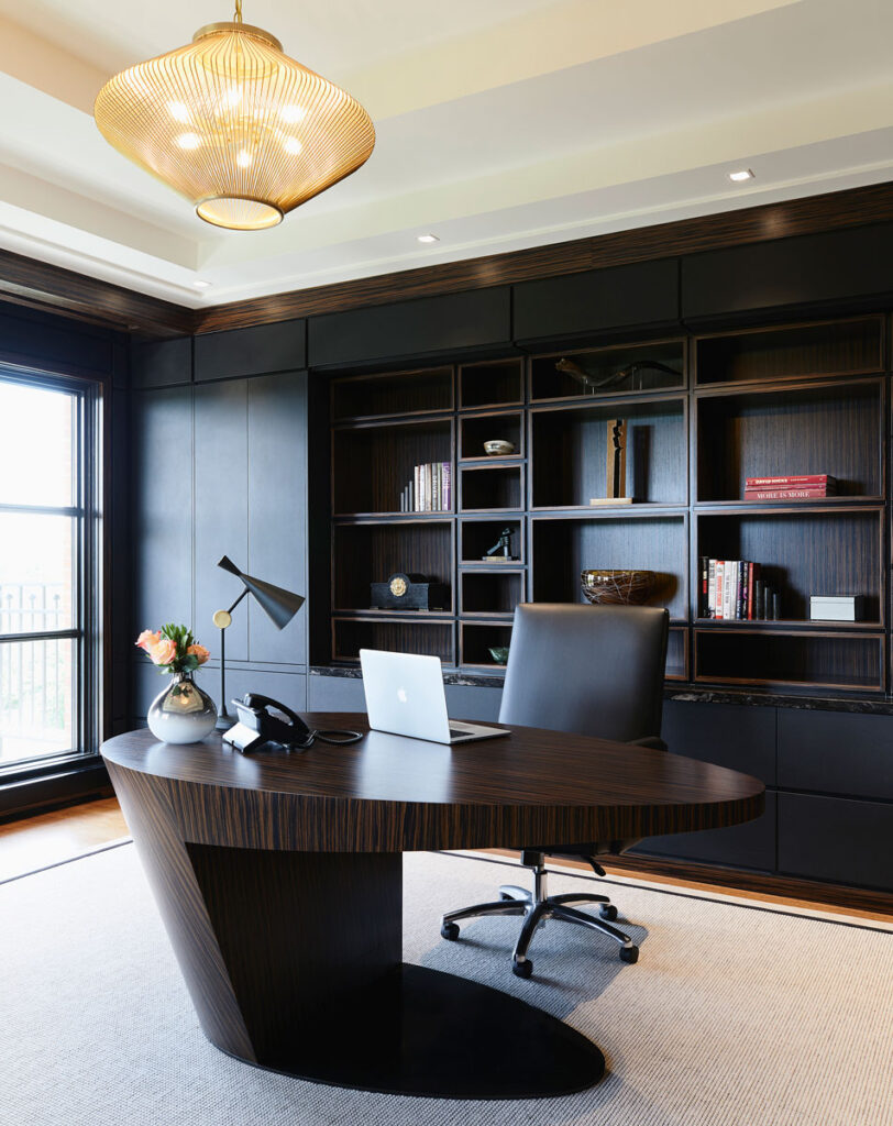 Home office with black millwork and a gold mesh light fixture.