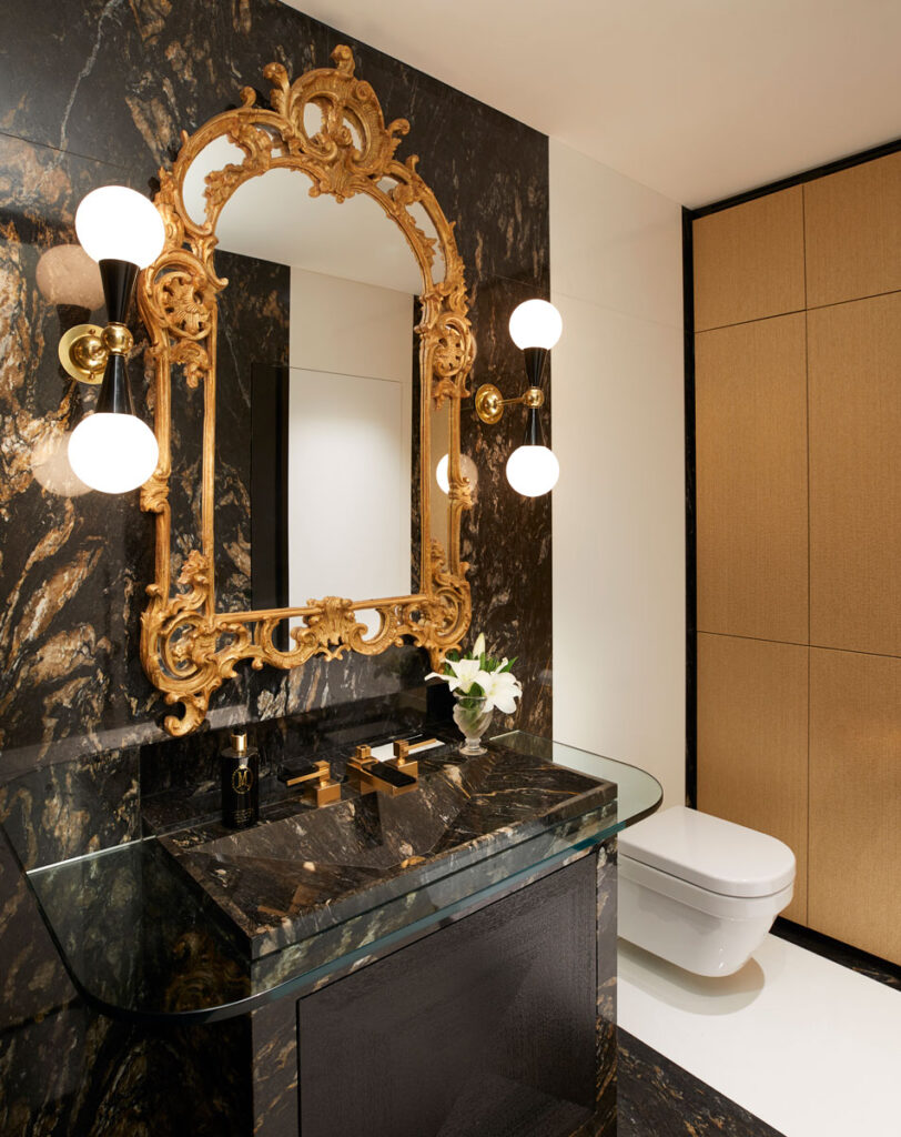 Opulent bathroom with gold and black quartzite and an ornate gold mirror.