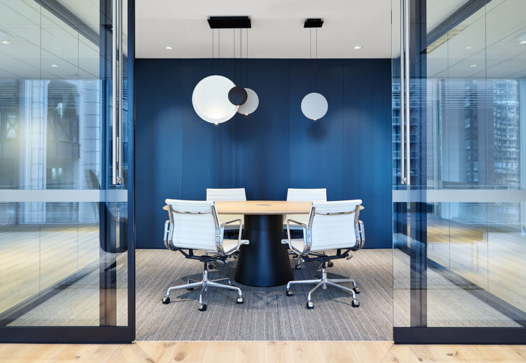 Glass walled meeting room with blue walls and moder light fixture.