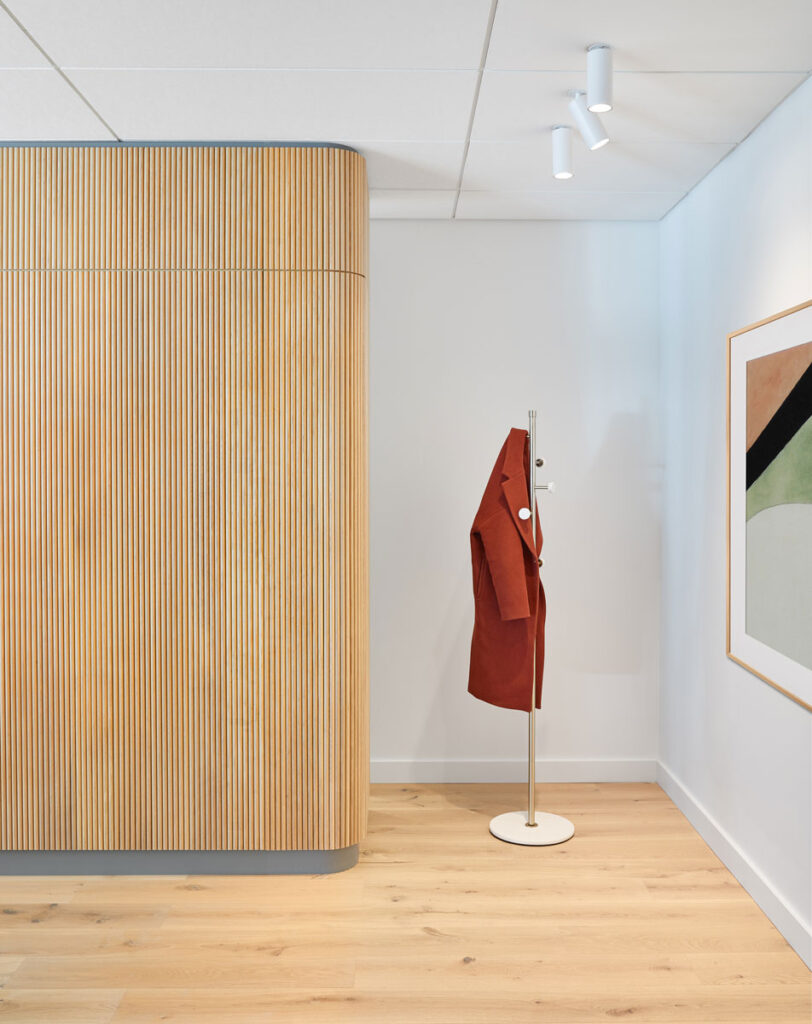 Coat hanging area with tambour wall installation and modern art.