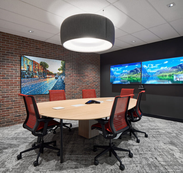 A black drum light is suspended above a round boardroom table with red office chairs.