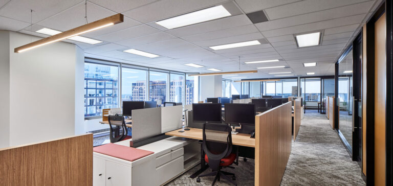 Open plan office with wood panelled dividers.
