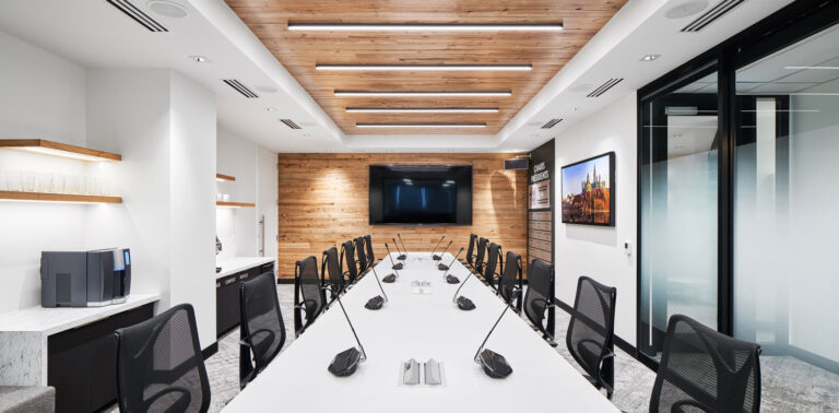 Modern boardroom with long white boardroom table and a wood panelled ceiling.