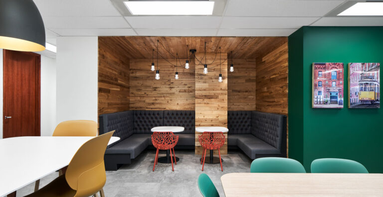 Wood panelled break room with bench seating and black pendant lights.