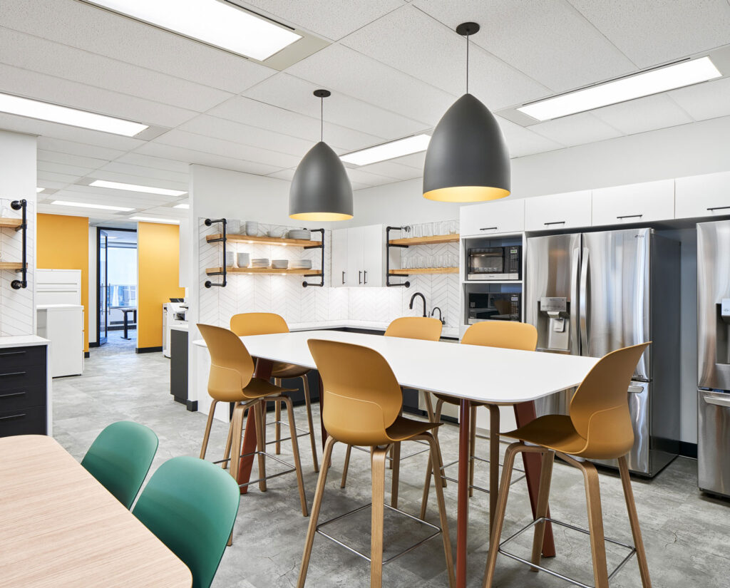 Modern white breakroom with colourful chairs.
