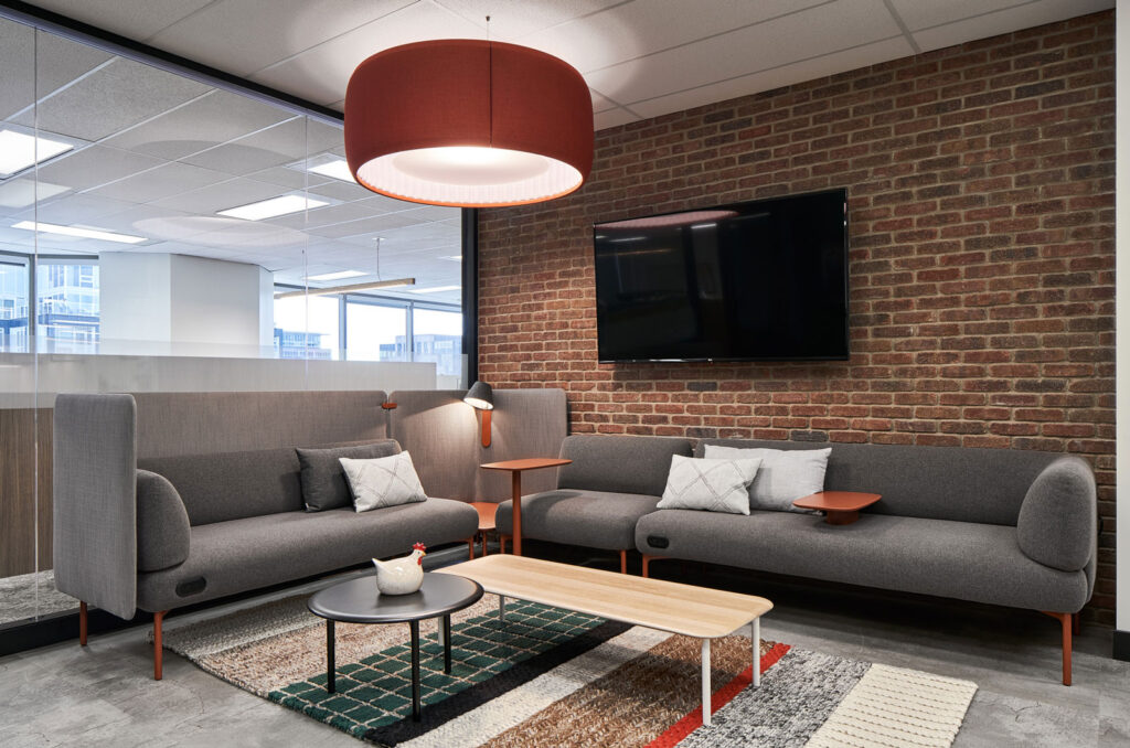 Brick panelled seating area with gray couches.