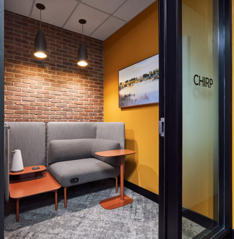 Focus room with seating options, brick wall and orange accent walls.