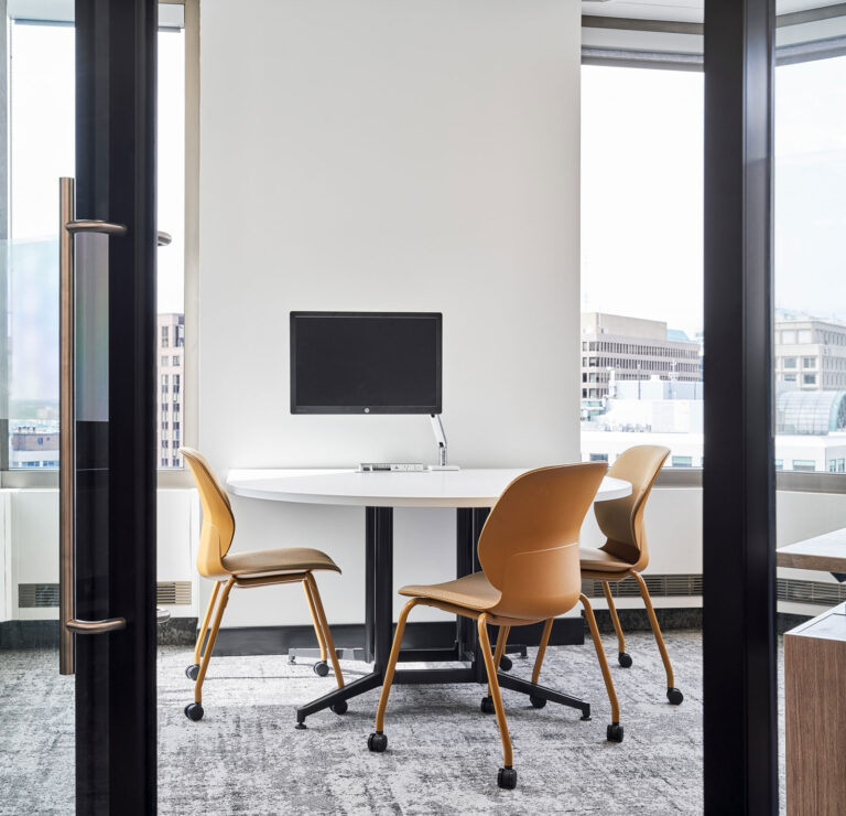 Office with white walls and gold chairs.